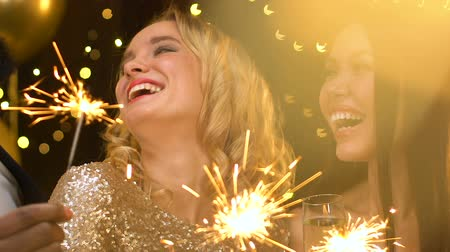 bengália : Pretty ladies holding bengal lights at christmas party, laughing and having fun