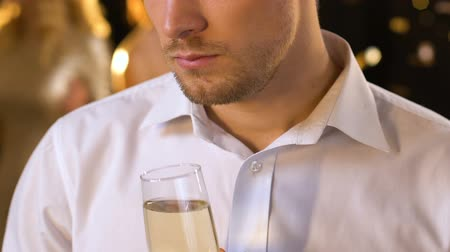 lights up : Upset handsome man feeling jealous at party, drinking alcohol and looking around
