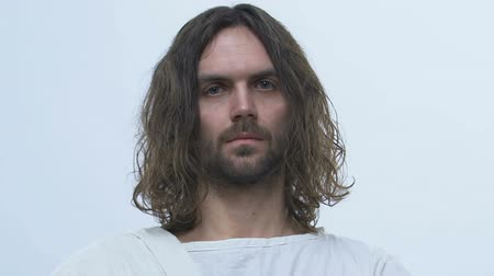 communion : Man alike Jesus standing on light background, looking into camera, messiah