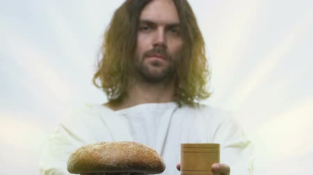 communion : Man alike Jesus holding loaf of bread and glass of vine in hands. Stock Footage