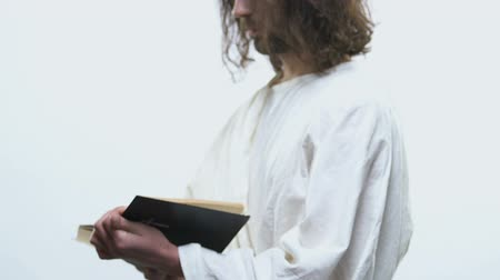 verse : Man in white robe opening Bible and looking into camera, answers in belief