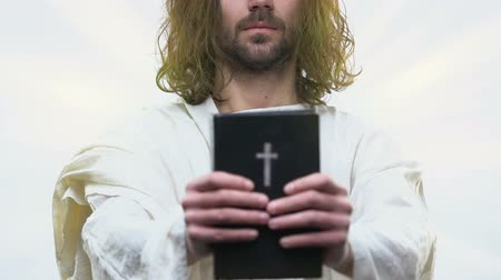 bible study : Preacher in white robe holding holy Bible in hands against bright background Stock Footage