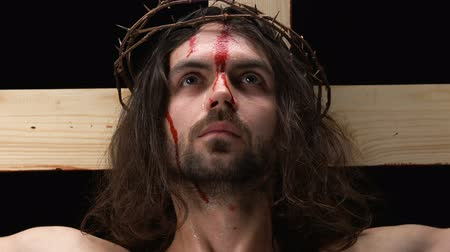 megmentő : Crying Jesus Christ with bleeding face looking at camera, crucifixion on cross Stock mozgókép