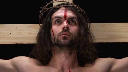 bibliai : Jesus with bleeding body crucified on cross and looking to heaven, close-up