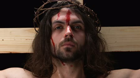 bibliai : Crying Jesus with bleeding face looking at camera, punishment for sins, close-up