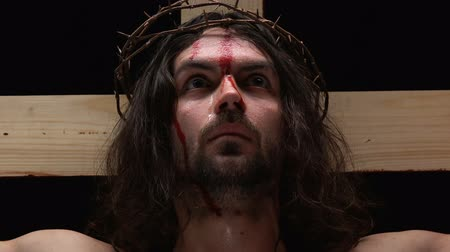 crucified : Frightened Jesus Christ with bleeding body crucified on cross looking at camera