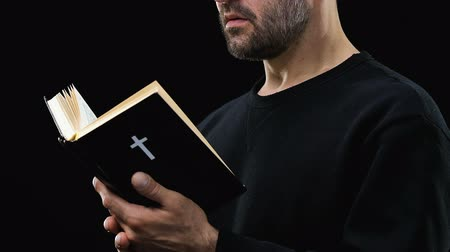 testament : Bearded man reading holy bible, praying God against dark background.