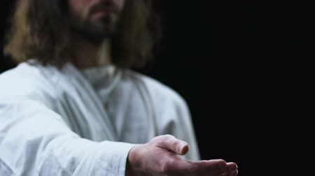 евангелие : Jesus Christ reaching out his hand against dark background, helping people Стоковые видеозаписи