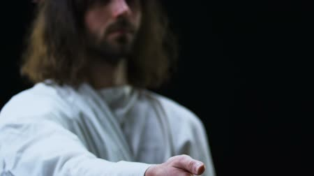 jézus : Jesus Christ stretching helping hand against black background, faith and belief