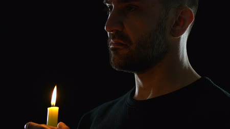 pena : Young man looking to heaven and blowing candle, blessing God, dark background Vídeos