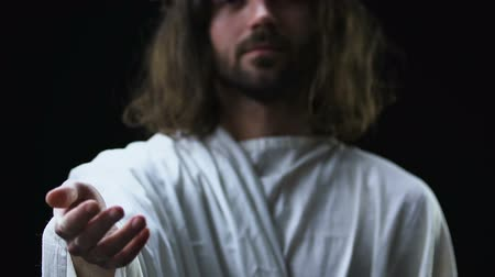 evangélium : Kind Jesus Christ stretching helping hand against dark background, christianity