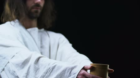 crucified : Jesus Christ showing cup of water to camera, helping poor people charity concept
