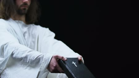падуб : Jesus in robe showing holy bible to camera, faith and belief, dark background