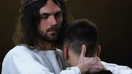 zsidó : Jesus hugging young miserable man and looking at camera, forgiving sins Stock mozgókép