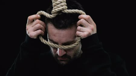 предложение : Desperate man wearing loop on neck, suicide prevention concept, risk of death