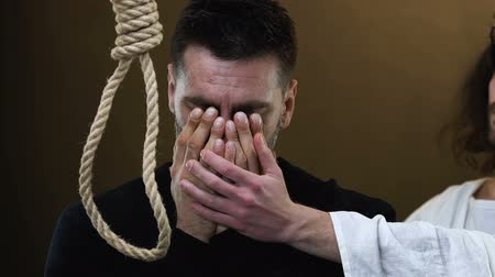 acreditar : Jesus supporting crying desperate man standing near rope with hangmans noose