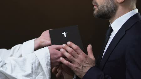 bible black : Priest giving business man holy bible against black background, Christianity