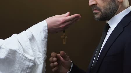jewish prayer : Priest giving male political wooden cross against black background, Christianity