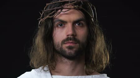 resurrection : Crying Jesus Christ in crown if thorns looking at camera against dark background