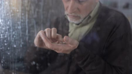 maliyetleri : Unhappy male pensioner counting coins hand, old age poverty, social instability