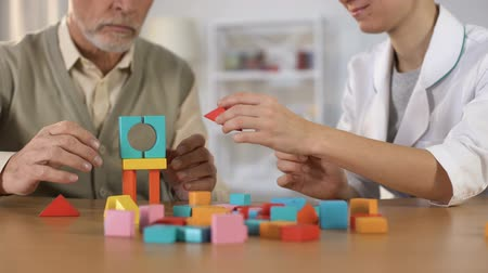 zihinsel : Hospital worker helping dementia patient combine color blocks, brain exercise Stok Video
