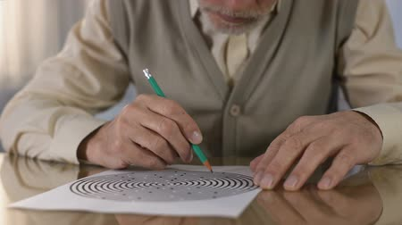 habilidade : Concentrated retired man solving logic test at table, memory exercise, neurology