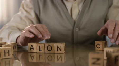 gepensioneerd : Old wrinkled male making word alone of wooden cubes on table, nursing home Stockvideo