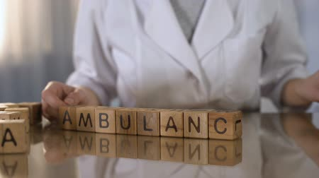 clínico : Female doctor making word ambulance of wooden cubes, urgent medical service
