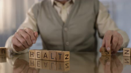 nursing : Grandfather making word health of wooden cubes on table, elder care, medicine Stock Footage