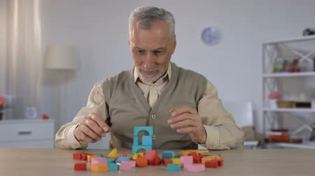 scena : Positive old man playing with wooden cubes, cognitive training in Alzheimer