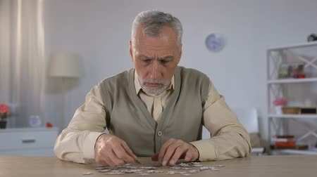 psikoloji : Old man exercises with puzzle, suffers cognitive impairment, Alzheimer symptom Stok Video