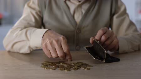 precisão : Pensioner putting few coins into wallet, poverty concept, low social welfare