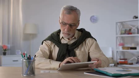 nyugta : Old man entering data from checks into tablet, counting budget and savings