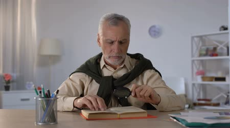 catalog : Senior man reading book with magnifying glass, attention to details, erudition