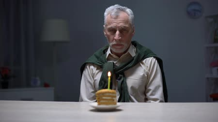 grandad : Sad granddad celebrating lonely birthday with piece of cake, forgotten by family Stock Footage
