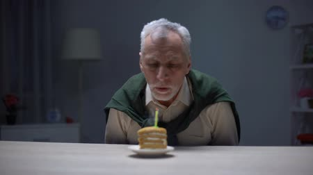 grandad : Lonely old man blowing candle on piece of cake, celebrating lonely birthday