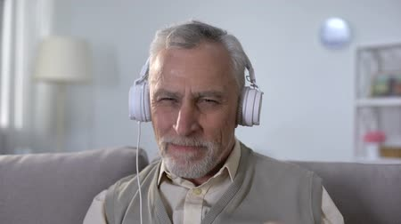 old radio : Positive old man in headphones listening to rock song, heavy metal from youth Stock Footage
