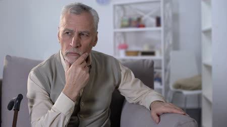 health insurance : Upset old man sitting on couch, thinking over health problems, low pensions