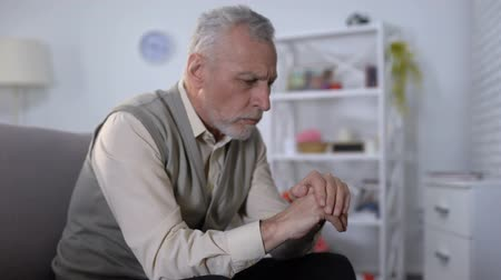 aflição : Old man looking at hand trembling, distressed by tremor, early Alzheimer symptom Stock Footage