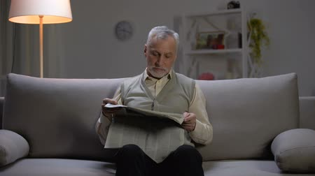 článek : Pensioner reading newspaper in evening, looking surprised from breaking news