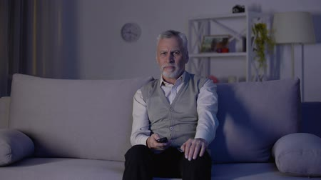 tv channel : Old man switching channels with remote control, bored and annoyed with ads