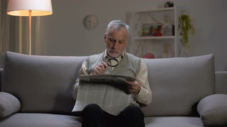 gentleman : Senior man reading newspaper with magnifier, sitting on couch, eyesight problems