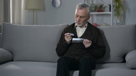 arriscado : Old man reading leaflet with instructions for medication, risky self-treatment