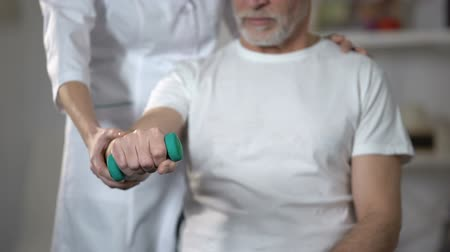 inválido : Nurse helping pensioner to lift dumbbell, rehabilitation center after insult
