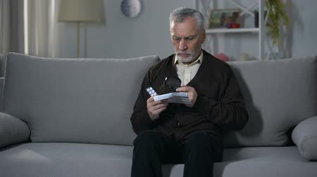 suplementy : Old man reading instruction for pills with magnifier, treating vision impairment