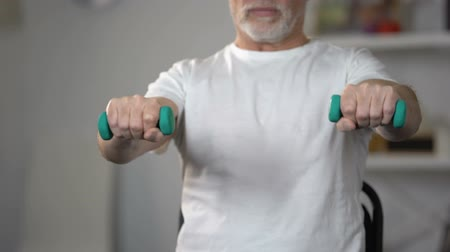 insult : Old man lifting dumbbells, training muscles and joints after injury or insult