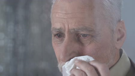 rebuliço : Old man wiping tear with napkin looking at rainy weather outside, anguish Stock Footage