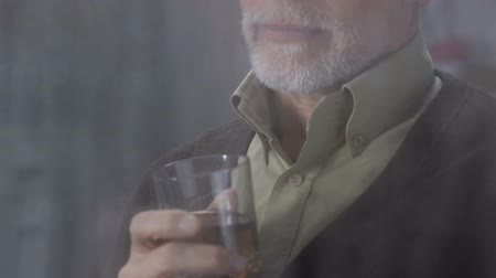 bourbon whisky : Gentleman slowly drinking whiskey at home, enjoying rainy weather outside window