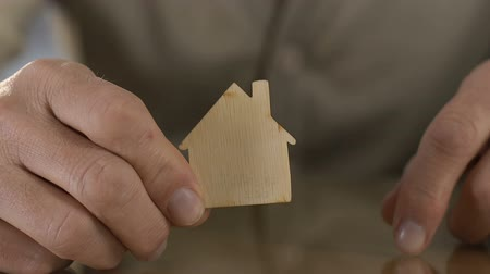 doação : Mature man holding wooden figure of house before camera, missing home in hospice