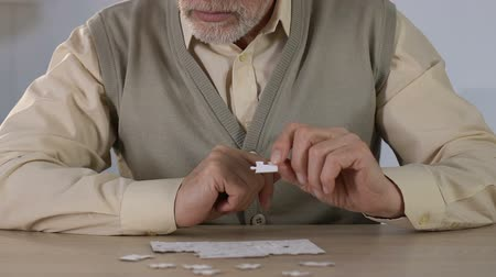 kiegészítés : Old man combining jigsaw puzzles at rehab, activity for memory development